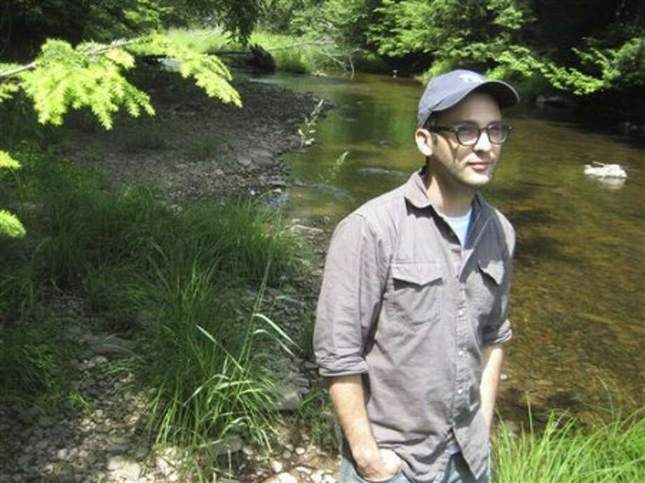 "In this June 15, 2010 photo, filmmaker Josh Fox poses along a stream running through his property in Milanville, Pa. Fox''s new documentary, ""Gasland,"" takes on the natural gas drilling industry. (AP Photo/Michael Rubinkam)"