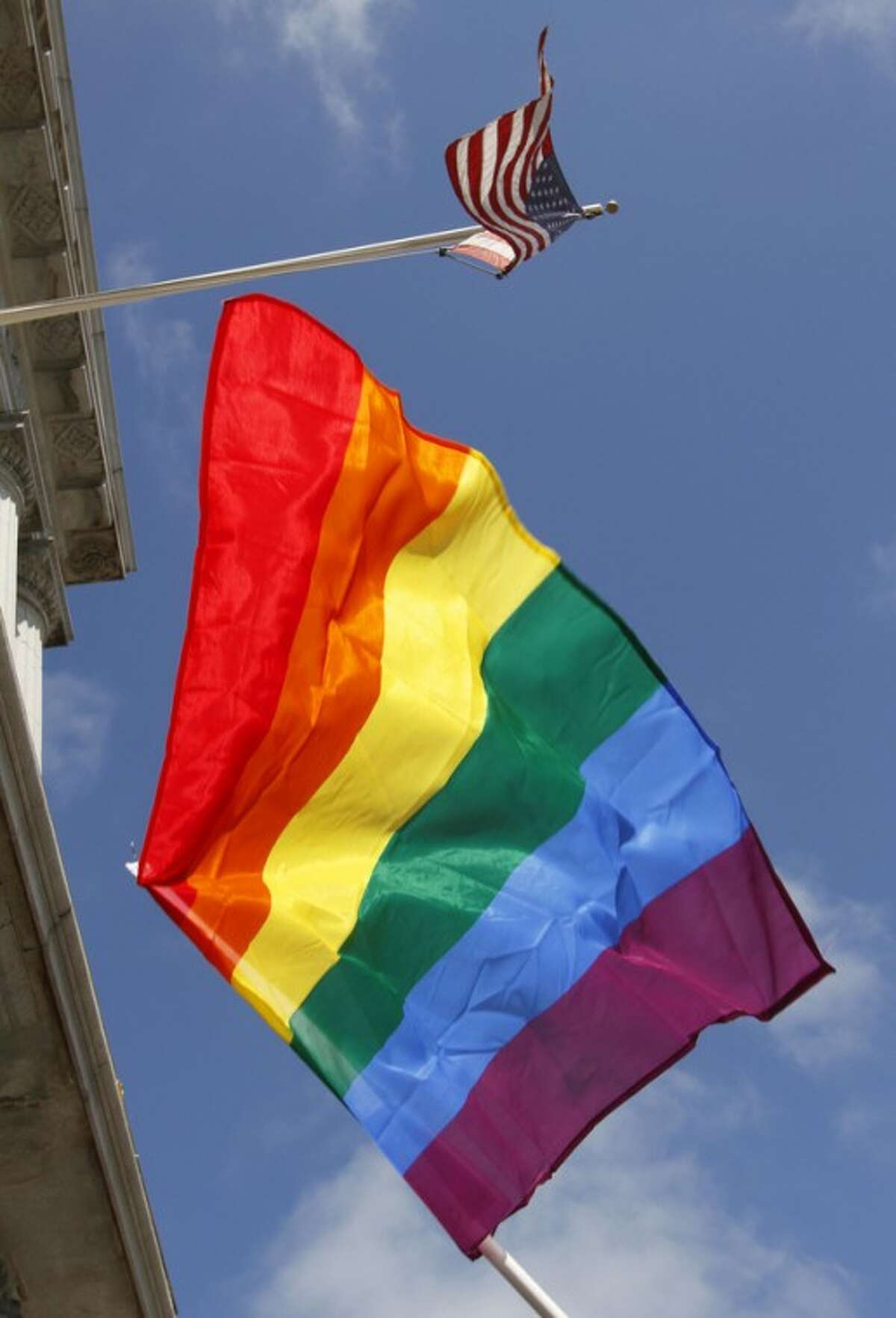 In this file photo from Thursday, Aug. 12, 2010, a rainbow flag flies below the American flag outside City Hall in San Francisco. The U.S. Supreme Court decided Friday, Dec. 7, 2012, to hear the appeal of a ruling that struck down Proposition 8, the state?'s measure that banned same sex marriages. The highly anticipated decision by the court means same-sex marriages will not resume in California any time soon. The justices likely will not issue a ruling until spring of next year. A federal appeals court ruled in February that Proposition 8?'s ban on same-sex marriage was unconstitutional. But the court delayed implementing the order until same-sex marriage opponents proponents could ask the U.S. Supreme Court to review the ruling. (AP Photo/Ben Margot)