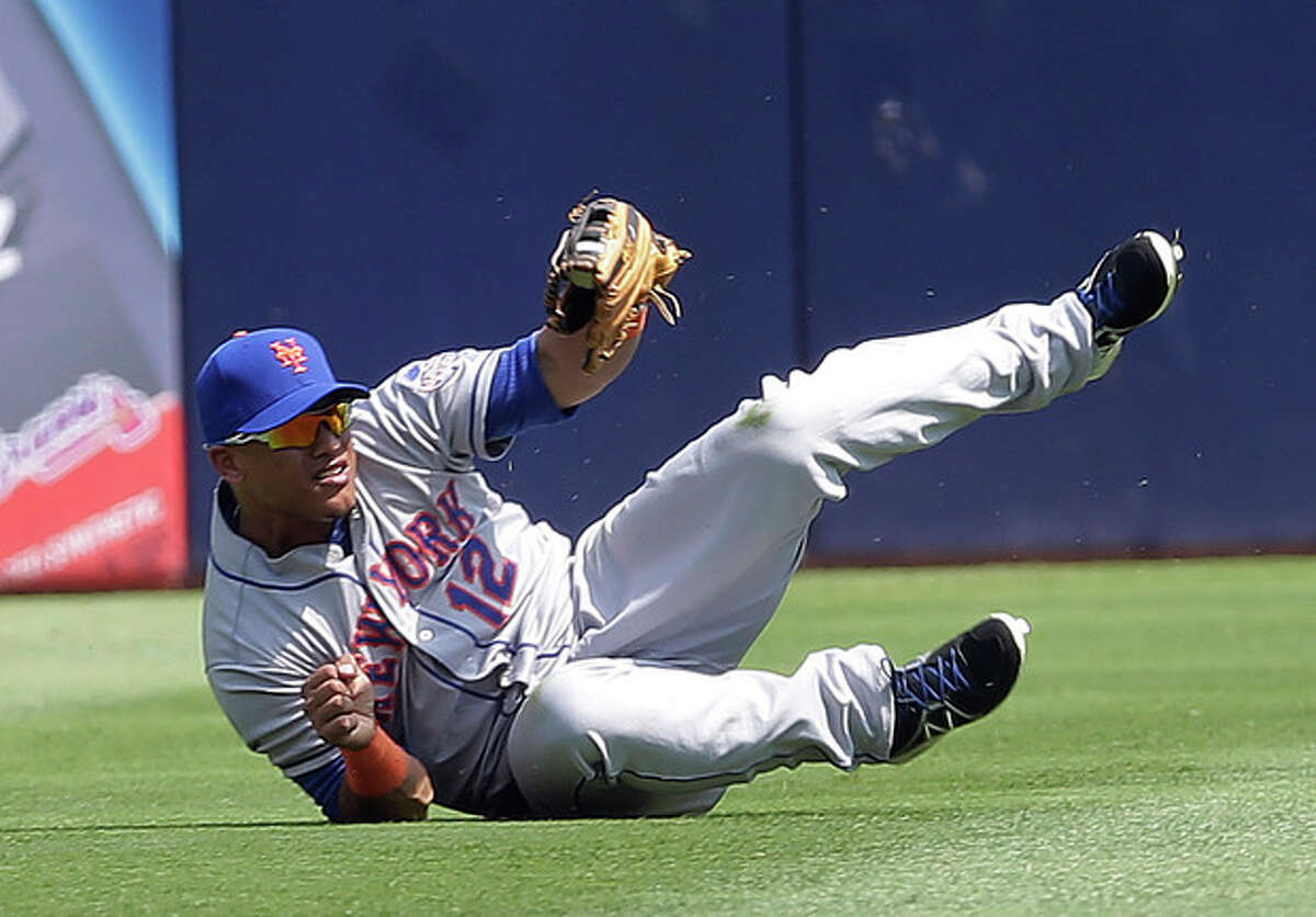 New York Mets center fielder Juan Lagares (12) gets to his feet after making a catch on a fly ball by Atlanta Braves' Justin Upton in the first inning of a baseball game Wednesday, Sept. 4, 2013 in Atlanta. (AP Photo/John Bazemore)