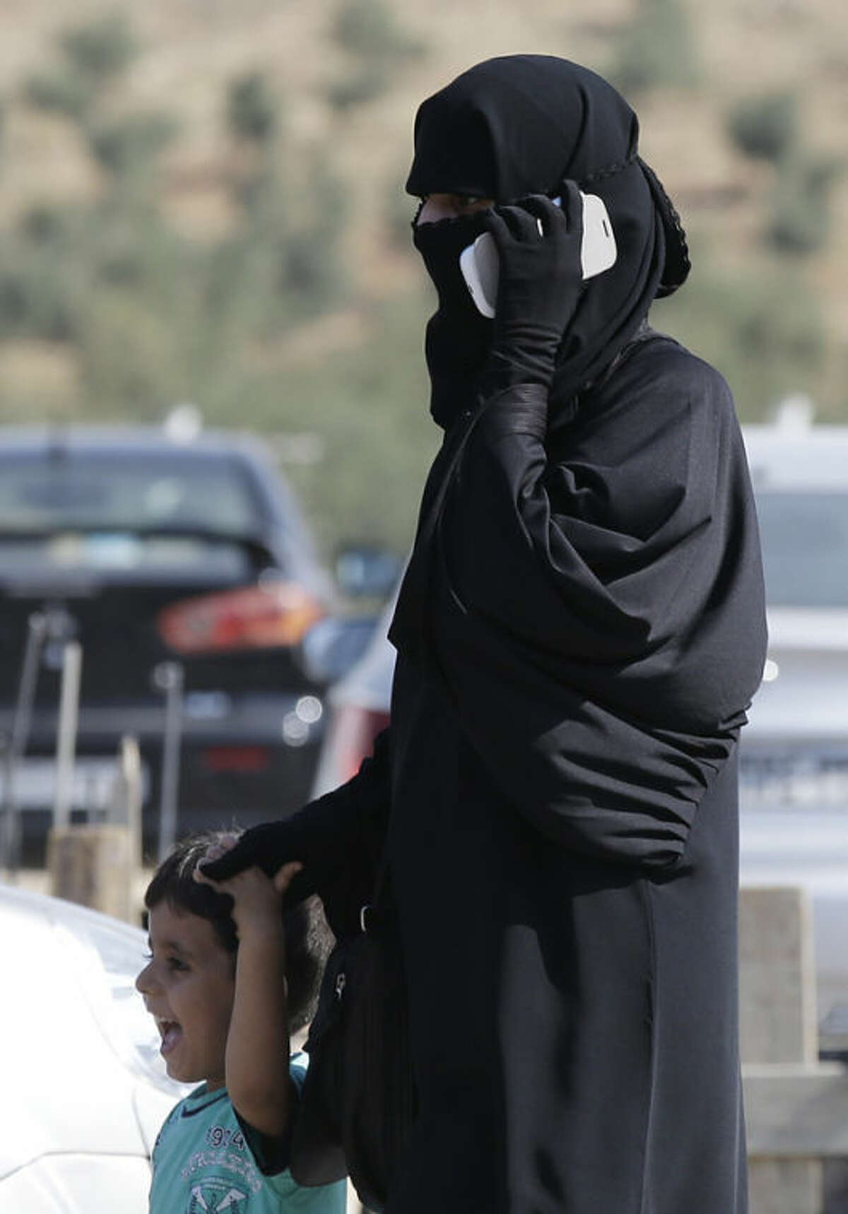 A Syrian refugee uses a mobile phone as she walks with a child after crossing the Turkish Cilvegozu gate border, Monday, Sept. 2, 2013. U.S. President Barack Obama is inviting former foe Sen. John McCain to the White House, hoping one of Congress' most intractable foreign policy hawks will help sell the idea of a U.S. military intervention in Syria to a nation deeply scarred by more than a decade of war. (AP Photo/Gregorio Borgia)