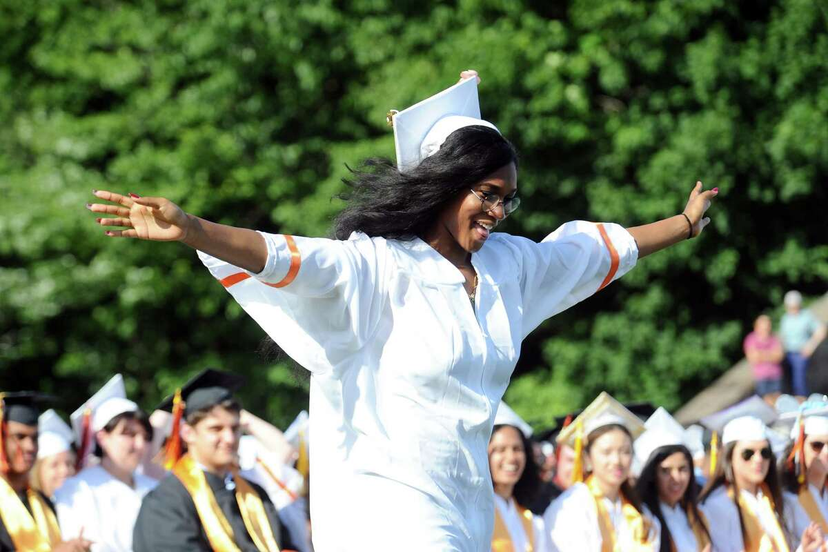 Juni Pun walks towards the stage with her arms outstretched to receive her diploma during the Stamford High School graduation on Wednesday, June 15, 2016.