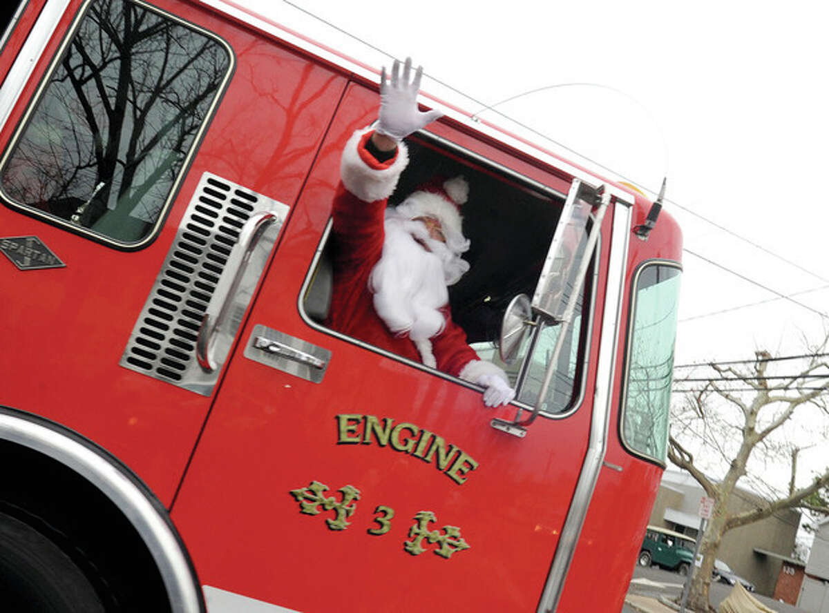 Hour photo / Matthew Vinci Santa arrives Sunday at the Rowayton firehouse where toys were donated to benefit the Carver Christmas party.