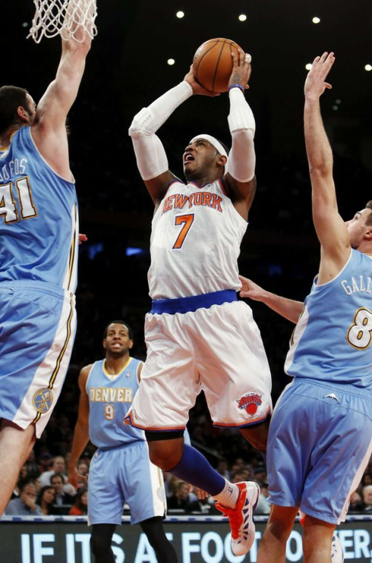 New York Knicks' Carmelo Anthony (7) shoots against Denver Nuggets' Kosta Koufus (41) and Danilo Gallinari (8) during the first half of an NBA basketball game, Sunday, Dec. 9, 2012, in New York. (AP Photo/Jason DeCrow)