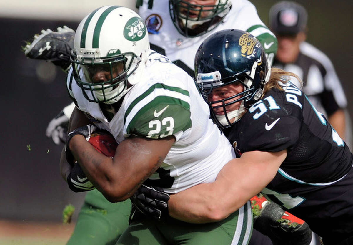 New York Jets running back Shonn Greene (23) is tackled by Jacksonville Jaguars middle linebacker Paul Posluszny (51) after a short gain during the first half of an NFL football game, Sunday, Dec. 9, 2012, in Jacksonville, Fla. (AP Photo/Stephen Morton)