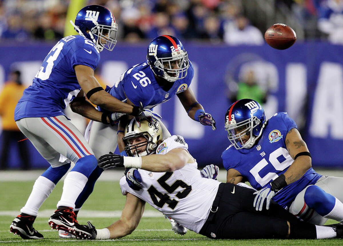 New Orleans Saints fullback Jed Collins (45) fumbles as New York Giants cornerback Corey Webster (23), Antrel Rolle (26) and Michael Boley (59) try to recover the ball during the first half of an NFL football game, Sunday, Dec. 9, 2012, in East Rutherford, N.J. (AP Photo/Kathy Willens)