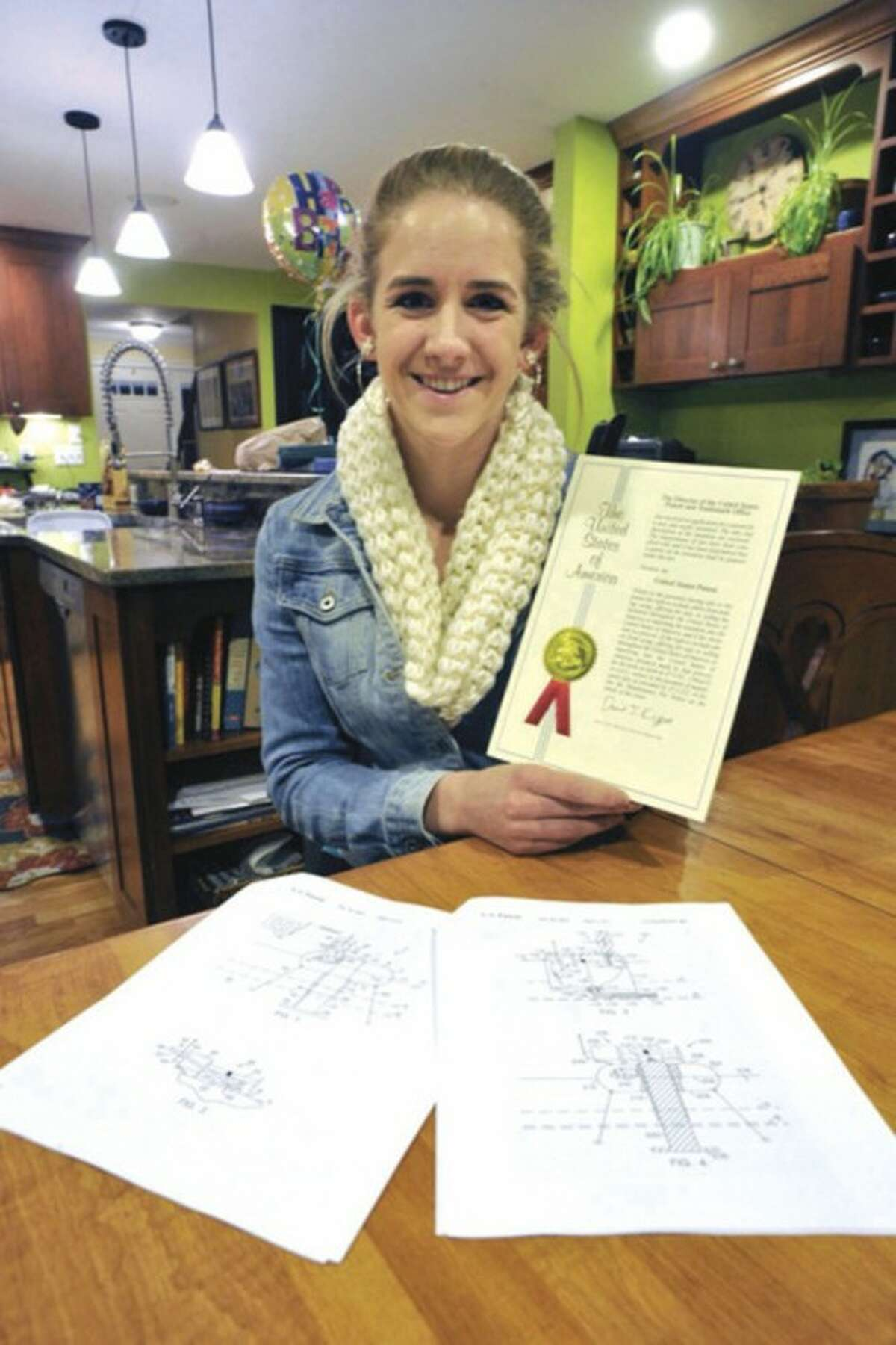 AP file photo / The News-Times, Jason Rearick In this Nov. 29 photo, Newtown High School senior Zoe Eggleston holds her patent certificate for the Ice Device, a machine she invented that monitors ice thickness on bodies of water, in Newtown.