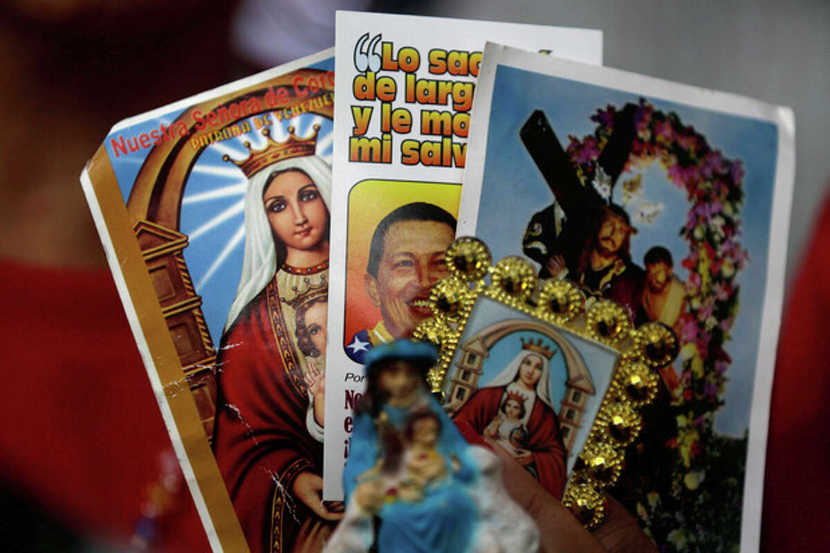 A person holds up an image of Venezuela's President Hugo Chavez among religious images during a demonstration in support of him at the Simon Bolivar square in Caracas, Venezuela, Sunday Dec. 9, 2012. Chavez was heading back to Cuba on Sunday for more cancer surgery after announcing that the illness returned despite two previous operations, chemotherapy and radiation treatment. Chavez said Saturday that if there are