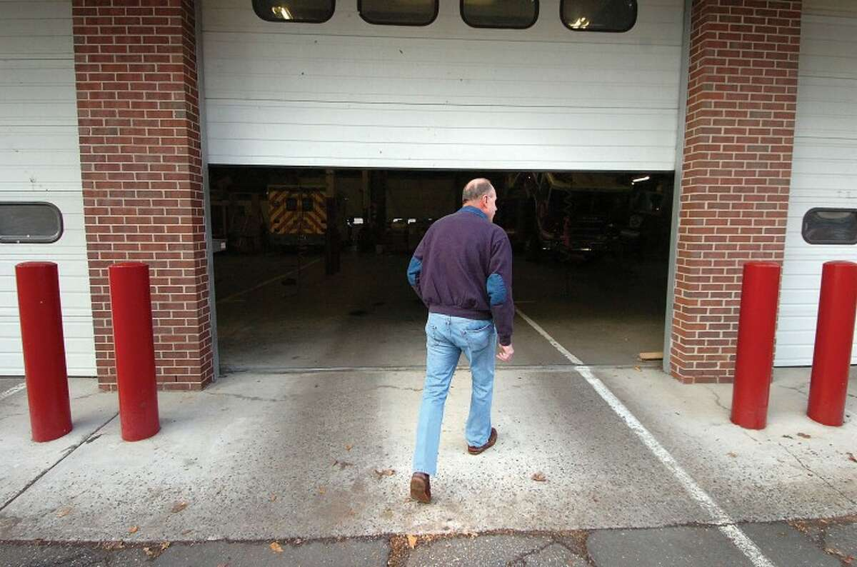 Hour Photo/Alex von Kleydorff. Recently retired Capt Karl Dolnier wlaks into a half open fire truck bay at Wilton Fire Headquaters.