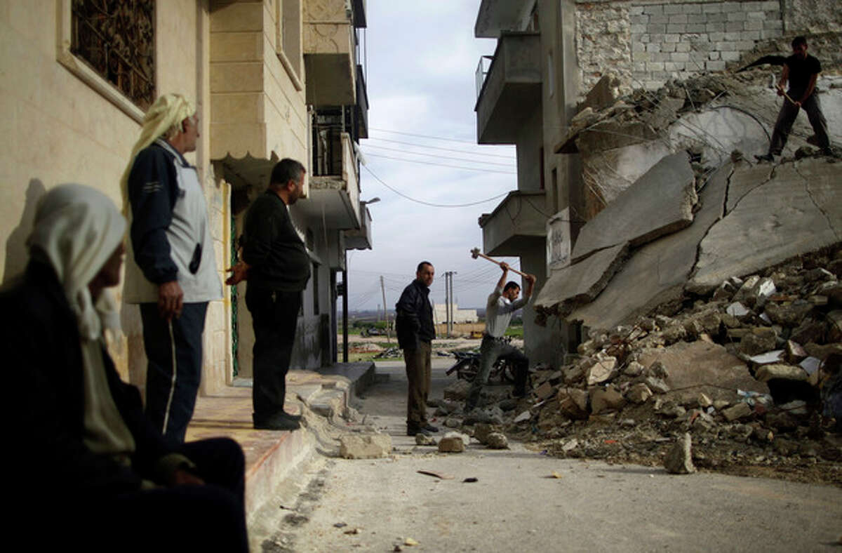 Syrian men use sledgehammers to break the concrete of a residential building destroyed in a government airstrike, while searching for belongings under the rubble, in Maaret Misreen, near Idlib, Syria, Wednesday, Dec. 12, 2012. (AP Photo/Muhammed Muheisen)