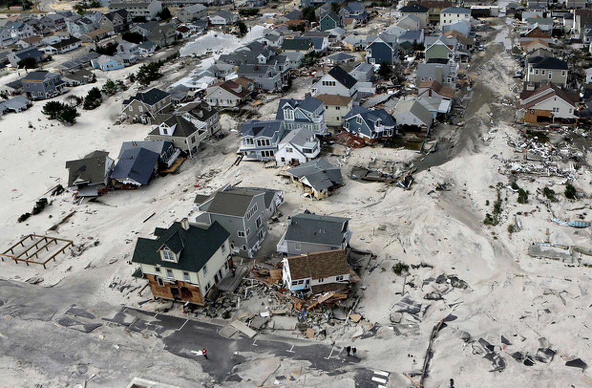 FILE - In an Oct. 31, 2012, file aerial photo, the destroyed and damaged homes are left in the wake of Superstorm Sandy in Ortley Beach, N.J. Researchers with the United States and British governments concluded Thursday Sept. 5, 2013, that climate change had made these events more likely: U.S. heat waves, Superstorm Sandy flooding, shrinking Arctic sea ice, drought in Europe's Iberian peninsula, and extreme rainfall in Australia and New Zealand. (AP Photo/Mike Groll, File)