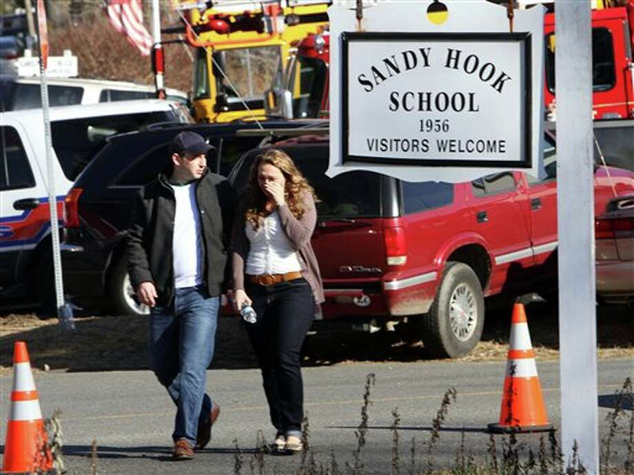 Parents walk away from the Sandy Hook Elementary School with their children following a shooting at the school, Friday, Dec. 14, 2012 in Newtown, Conn. A man opened fire inside the Connecticut elementary school where his mother worked Friday, killing 26 people, including 20 children, and forcing students to cower in classrooms and then flee with the help of teachers and police. (AP Photo/The Journal News, Frank Becerra Jr.) MANDATORY CREDIT, NYC OUT, NO SALES, TV OUT, NEWSDAY OUT; MAGS OUT / The Journal News