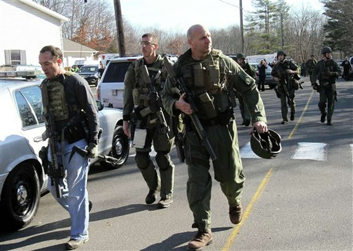 Heavily armed Connecticut State troopers are on the scene at the Sandy Hook School in Newtown, Conn. where authorities say a gunman opened fire, leaving 27 people dead, including 20 children, Friday, Dec. 14, 2012. (AP Photo/The Journal News, Frank Becerra Jr.) MANDATORY CREDIT, NYC OUT, NO SALES, TV OUT, NEWSDAY OUT; MAGS OUT