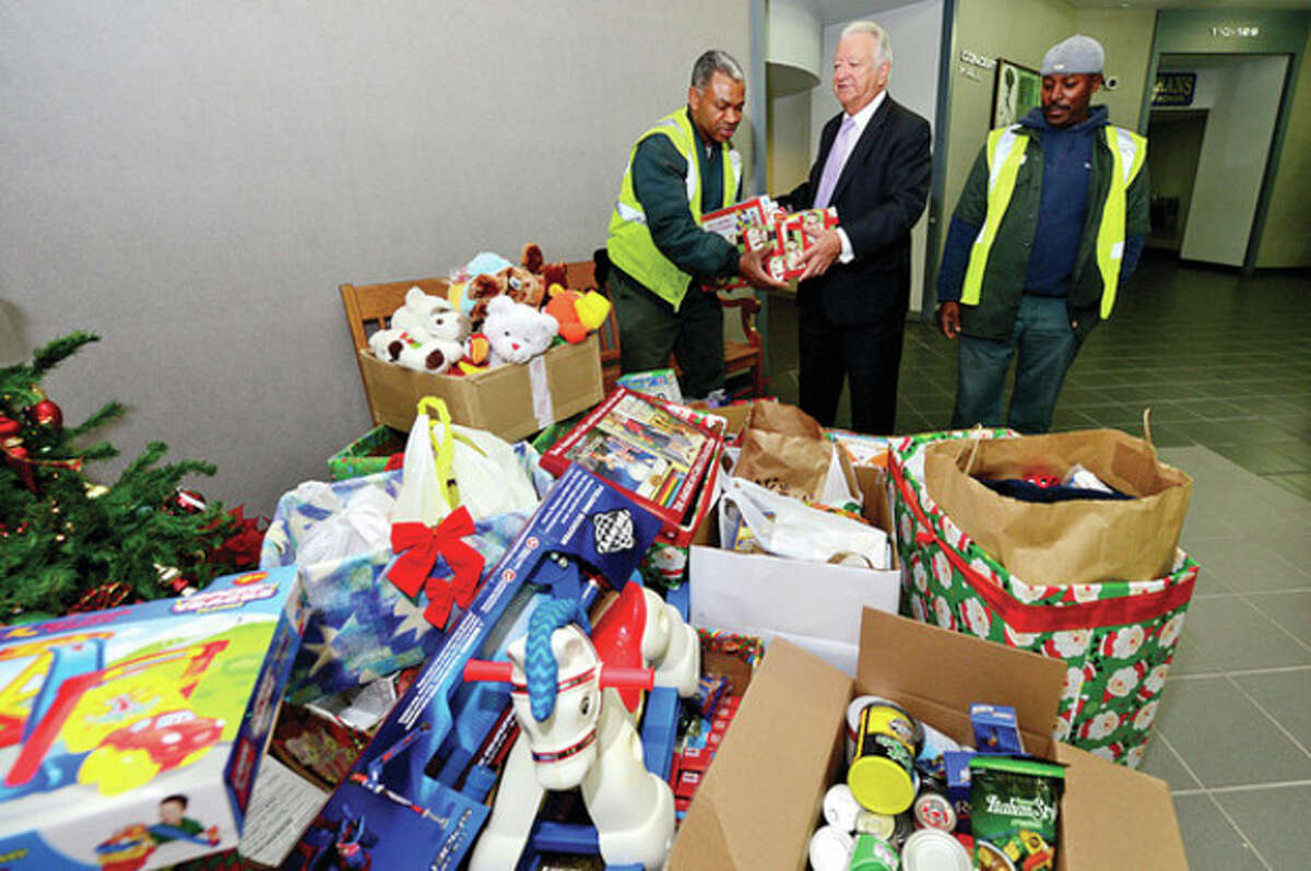 Mayor Moccia and and DPW workers Oliver Lawrence and Philip Senat load up presents at the city's Holiday Gift Giving Ceremony Thursday. Hour photo / Erik Trautmann