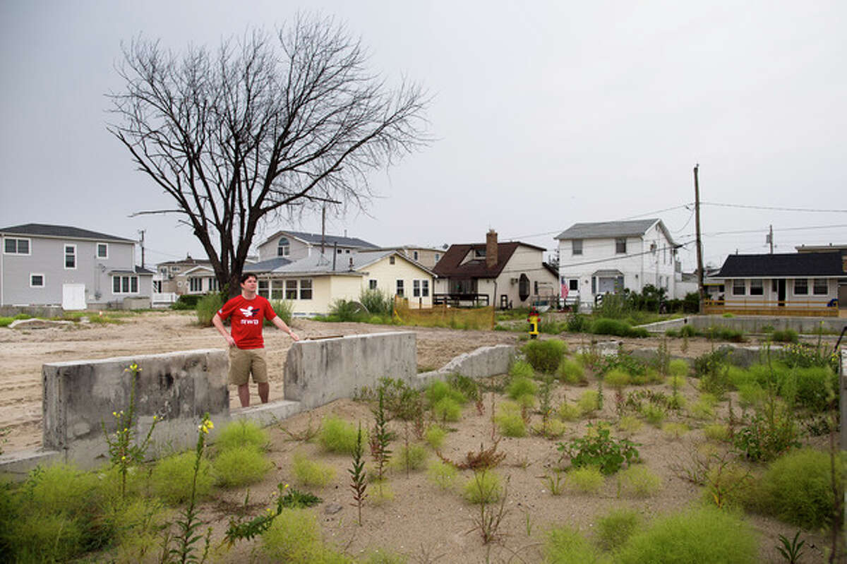 Joe Quinn visits the remains of his parents home that was destroyed by Superstorm Sandy, Monday, Sept. 2, 2013, in the Breezy Point neighborhood of New York. Quinn, whose older brother Jimmy was killed on the 104th floor of the World Trade Center?'s Tower One on Sept. 11, 2001, lost treasured pictures and hand-written letters from his brother that were among 12 boxes of mementos that were lost in the house when Superstorm Sandy struck the Queens community last October. (AP Photo/John Minchillo)