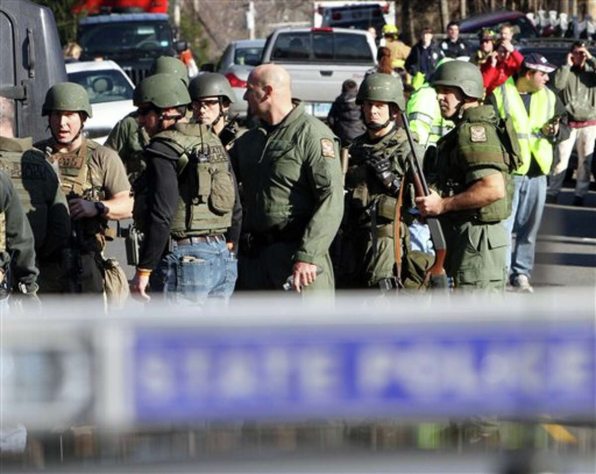 Heavily armed Connecticut State troopers are on scene at the Sandy Hook Elementary School following a shooting at the school, Friday, Dec. 14, 2012 in Newtown, Conn. (AP Photo/The Journal News, Frank Becerra Jr.) MANDATORY CREDIT, NYC OUT, NO SALES, TV OUT, NEWSDAY OUT; MAGS OUT