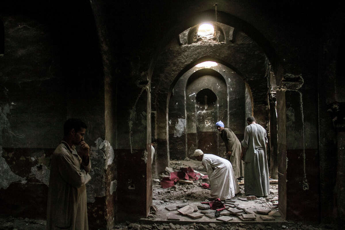 In this Sept. 3, 2013 photo, Egyptian Christian villagers clean up the damaged ancient chapel inside the Virgin Mary and St. Abraam Monastery that was looted and burned by Islamists, in Dalga, Minya province, Egypt. Dalga has been outside government control since hard-line supporters of the Islamist Mohammed Morsi drove out police and occupied their station on July 3, the day Egypt?'s military chief removed the president in a popularly supported coup. It was part of a wave of attacks in the southern Minya province that targeted Christians, their homes and businesses. (AP Photo/El Shorouk Newspaper, Roger Anis)