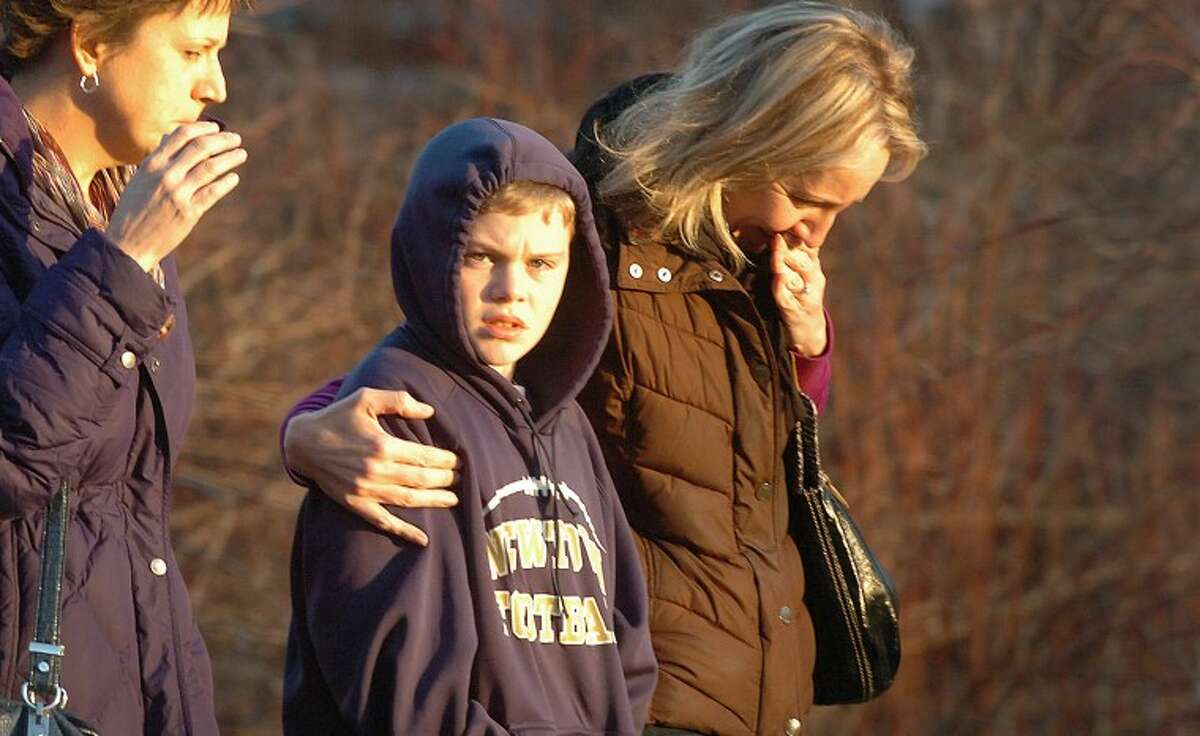 Hour Photo/Alex von Kleydorff. People leave the scene of a mass shooting at the Sandy Hook School in Newtown Ct. on Friday morning
