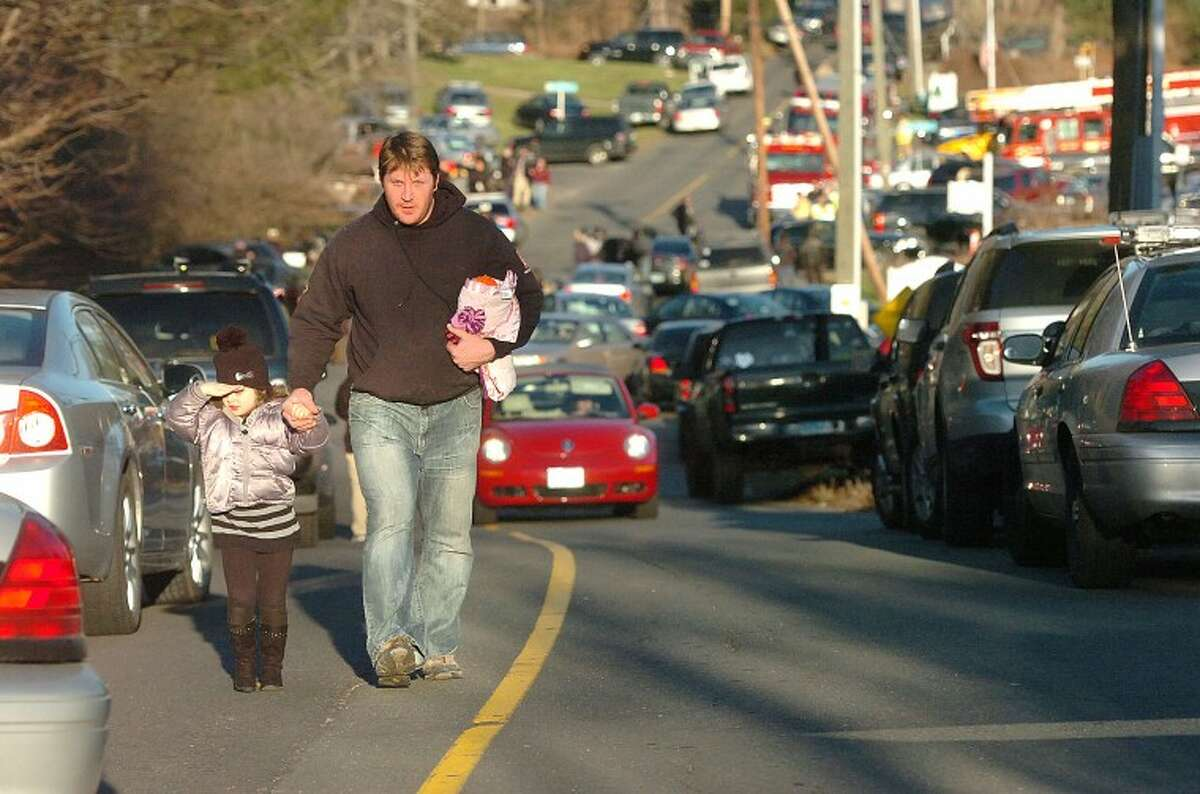 Hour Photo/Alex von Kleydorff. People leave the Sandy Hook Vol Fire Dept in Newtown Ct after a shooting massacre at The Sandy Hook School