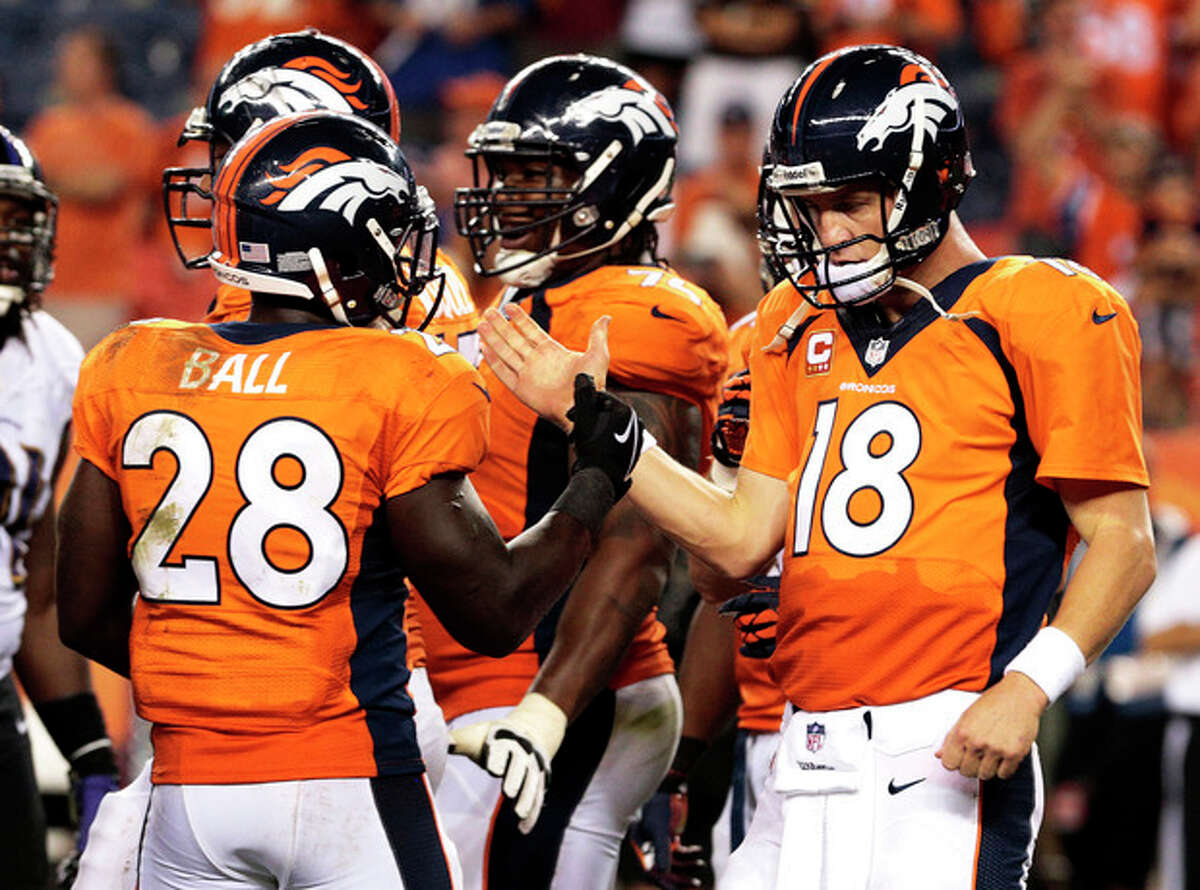 Denver Broncos quarterback Peyton Manning (18) greets teammate Montee Ball (28) as time expires in an NFL football game against the Baltimore Ravens, Thursday, Sept. 5, 2013, in Denver. The Broncos won 49-27. (AP Photo/Joe Mahoney)