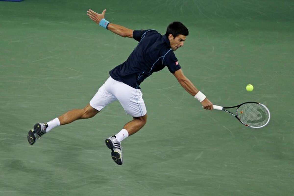 Novak Djokovic, of Serbia, leaps as he returns to Mikhail Youzhny, of Russia, during the men's quarterfinal round at the 2013 U.S. Open tennis tournament, Thursday, Sept. 5, 2013, in New York. (AP Photo/Charles Krupa)