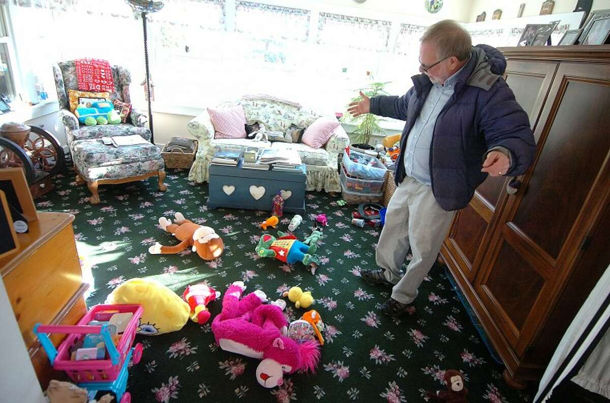 Hour Photo/Alex von Kleydorff. Gene Rosen stands in the sun room of his Sandy Hook home and shows the plush toys he gave to a group of kids from The Sandy Hook School after he took them inside after finding them on his front lawn.