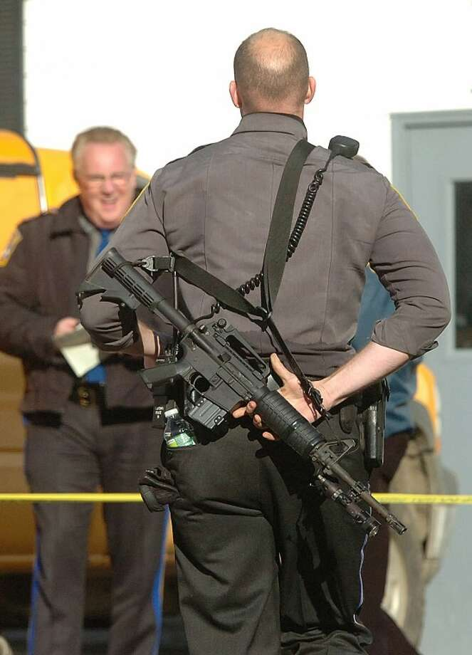 Hour Photo/Alex von Kleydorff. Arrmed first responders head into The Sandy Hook school after a mass shooting in Newtown Ct on Friday morning.