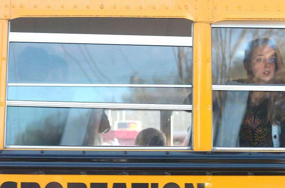 Hour Photo/Alex von Kleydorff. A school bus makes a stop near the Sandy Hook School in Newtown