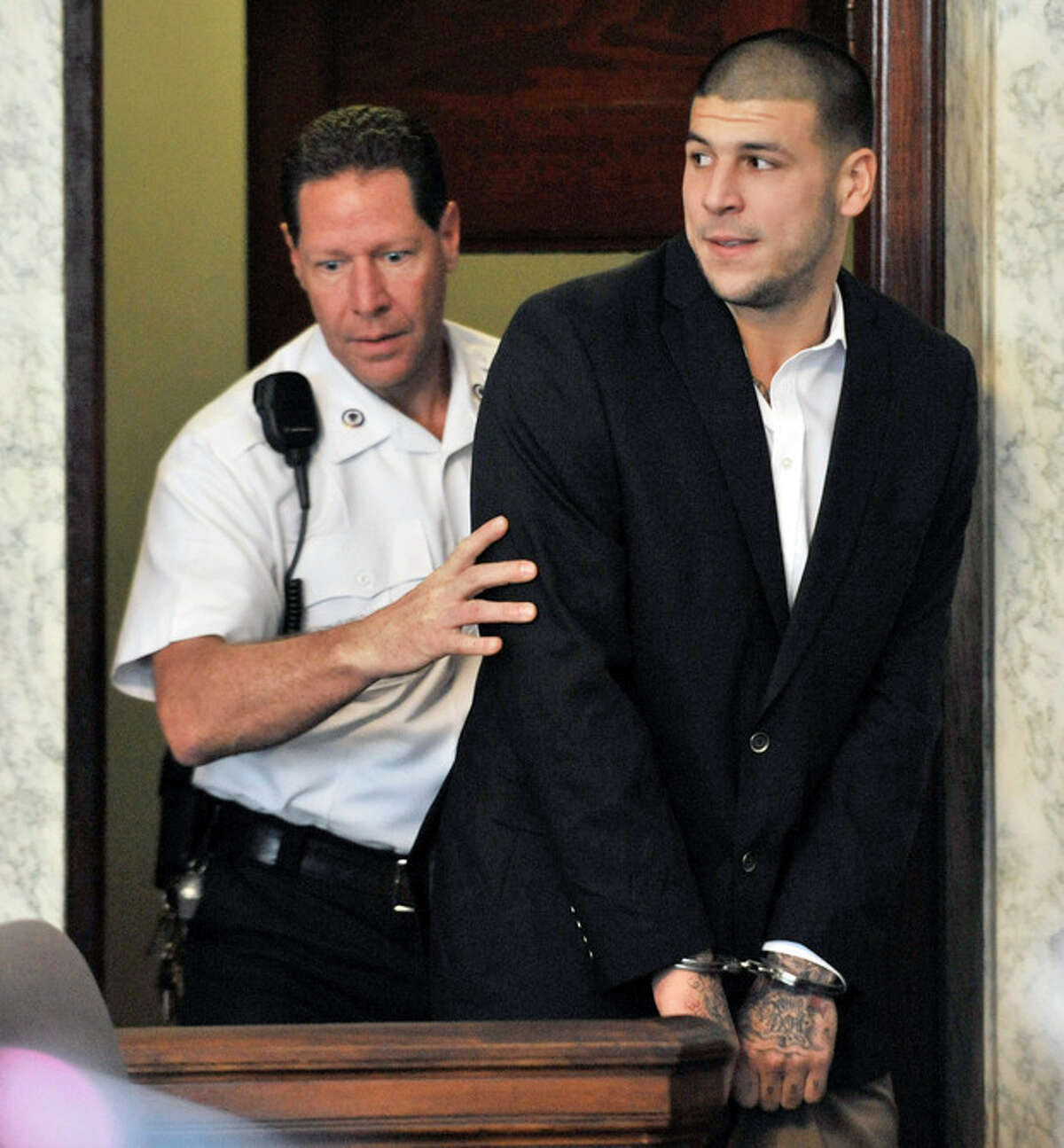 FILE - In this Aug. 22, 2013, file photo, former New England Patriots NFL football player Aaron Hernandez, is lead into court in Attleboro, Mass. Hernandez, who has been indicted on a murder charge in the killing of Odin Lloyd, is scheduled to face arraignment in Superior Court Friday, Sept. 6, 2013 in Fall River, Mass. (AP Photo/Josh Reynolds, File)