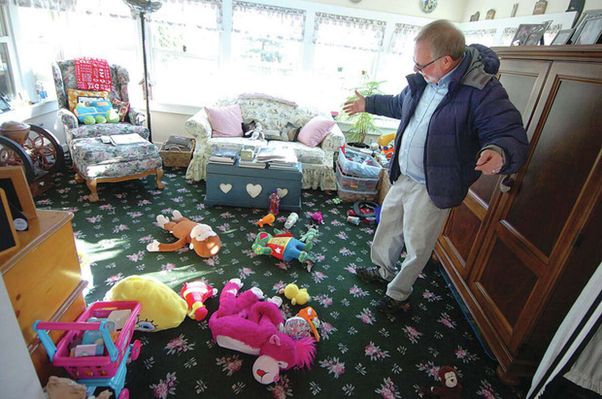 Hour photo / Alex von Kleydorff Gene Rosen stands in the sun room of his Sandy Hook home and shows the plush toys he gave to a group of kids from The Sandy Hook School after he took them inside after finding them on his front lawn.