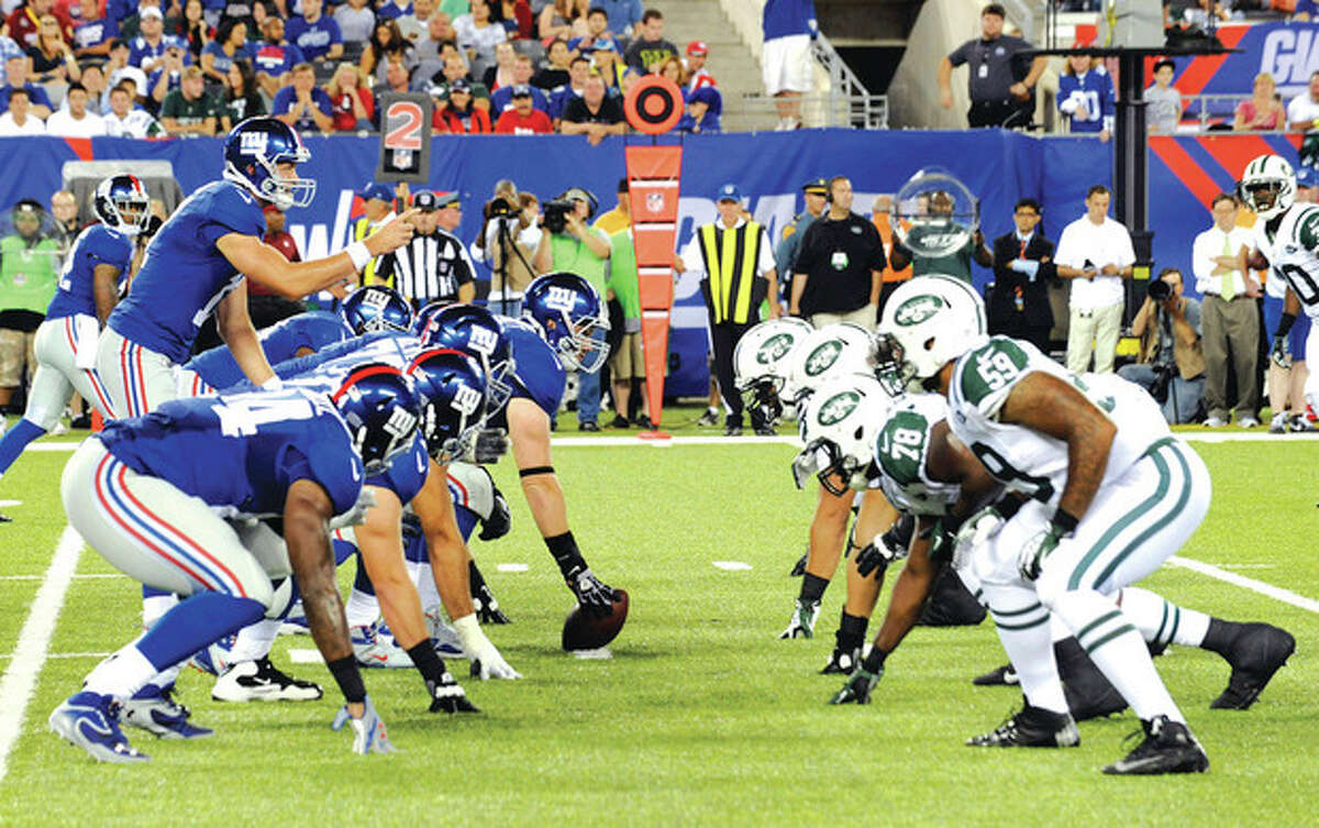 The New York Giants, left, line up against the New York Jets during overtime of a preseason NFL football game Saturday, Aug. 24, 2013, in East Rutherford N.J. (AP Photo/Bill Kostroun)
