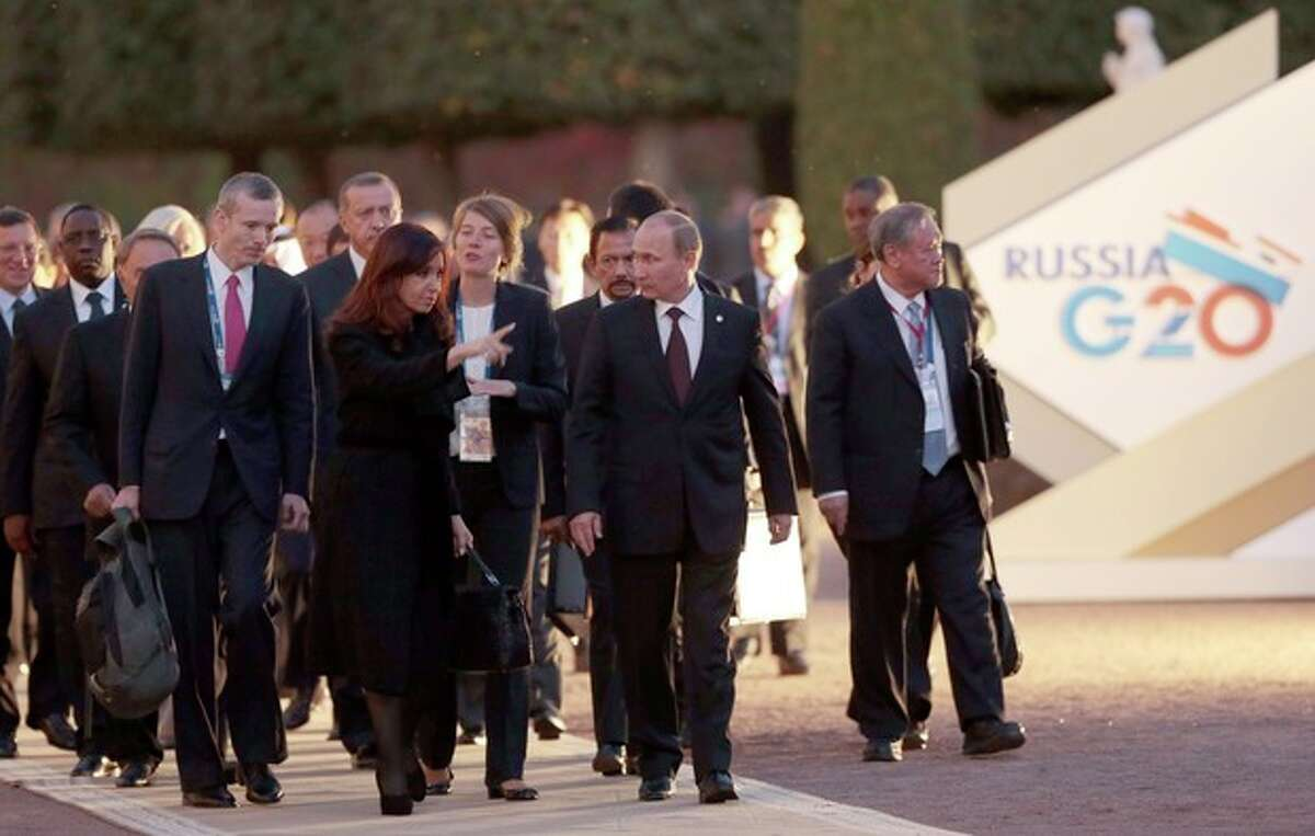 Russia's President Vladimir Putin, front center right, speaks with Argentina's President Cristina Fernandez de Kirchner, front center left, as they walk with other G-20 leaders toward a dinner at the Peterhof Palace in St. Petersburg, Russia on Thursday, Sept. 5, 2013. The threat of missiles over the Mediterranean is weighing on world leaders meeting on the shores of the Baltic this week, and eclipsing economic battles that usually dominate when the G-20 world economies meet. (AP Photo/Ivan Sekretarev)