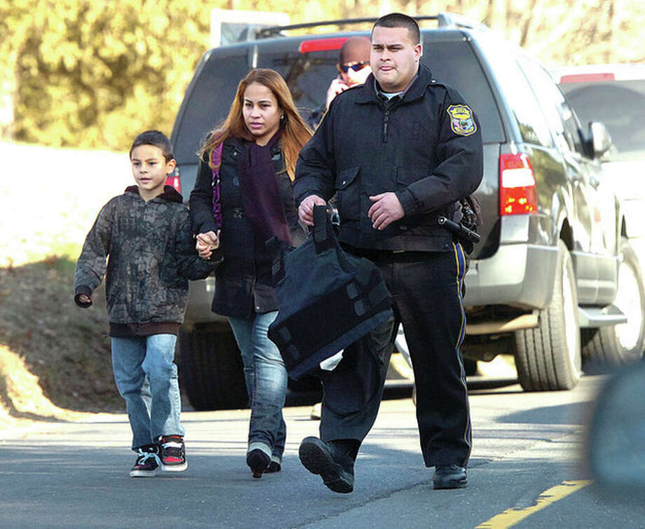 Hour Photo/Alex von Kleydorff. People are escorted by State Police away from the scene of a mass shooting at Sandy Hook School in Newtown Ct on Friday morning / 2012 The Hour Newspapers/Alex von Kleydorff