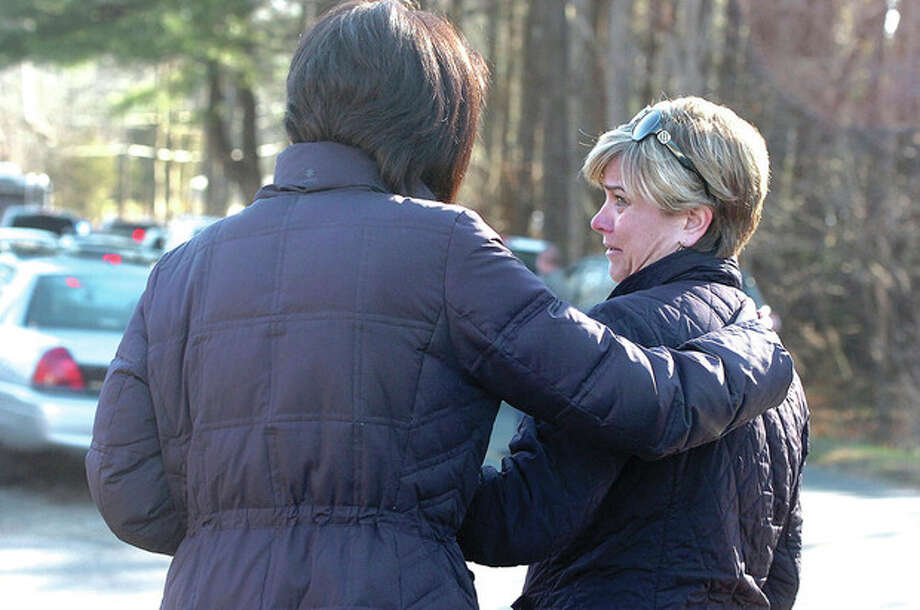 Hour Photo/Alex von Kleydorff. People are comforted near the scene of a mass shooting at Sandy Hook School in Newtown Ct on Friday morning. / 2012 The Hour Newspapers/Alex von Kleydorff
