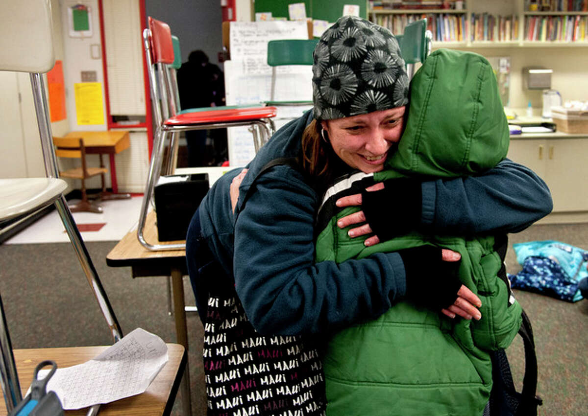 After watching TV news reports of the school shooting in Connecticut, Alicia Combo tightly hugs her son Morgan Askins at the close of school, Dec. 14, 2012, at Garfield Elementary in Spokane, Wash. A man killed his mother at their home and then opened fire Friday inside the elementary school where she taught, massacring 26 people, including 20 children, as youngsters cowered in fear to the sound of gunshots reverberating through the building and screams echoing over the intercom. (AP Photo/Spokesman Review, Dan Pelle)