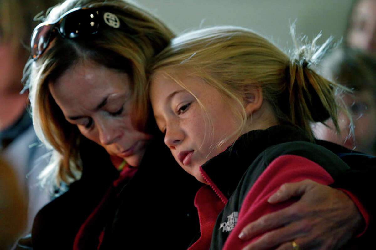 Molly Delaney, left, holds her 11-year-old daughter, Milly Delaney, during a service in honor of the victims who died a day earlier when a gunman opened fire at Sandy Hook Elementary School in Newtown, Conn., as people gathered at St. John's Episcopal Church , Saturday, Dec. 15, 2012, in the Sandy Hook village of Newtown, Conn. The massacre of 26 children and adults at Sandy Hook Elementary school elicited horror and soul-searching around the world even as it raised more basic questions about why the gunman, 20-year-old Adam Lanza, would have been driven to such a crime and how he chose his victims. (AP Photo/Julio Cortez)