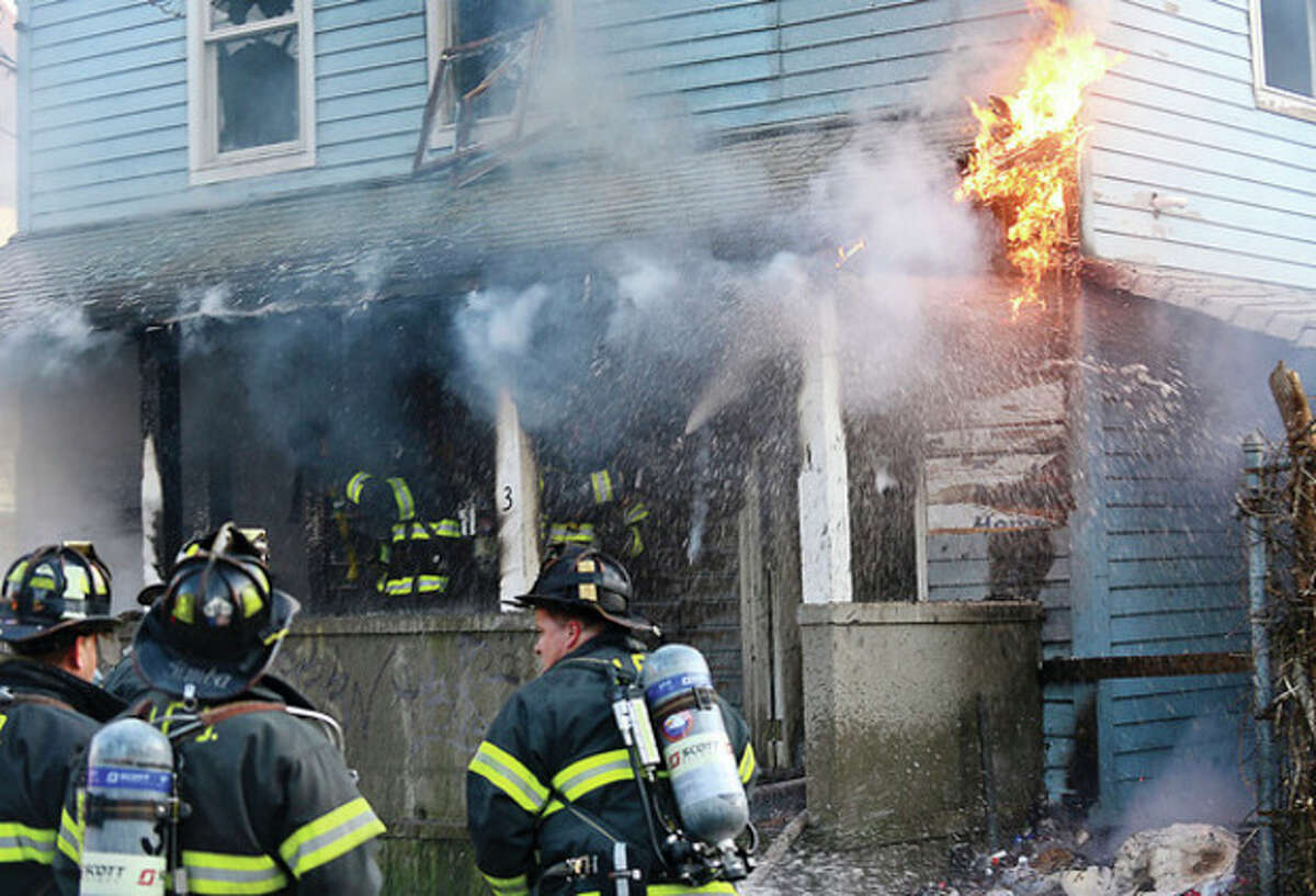 Norwalk firefighters respond to the scene of a house fire on Olean St Friday evening. Hour photo / Erik Trautmann