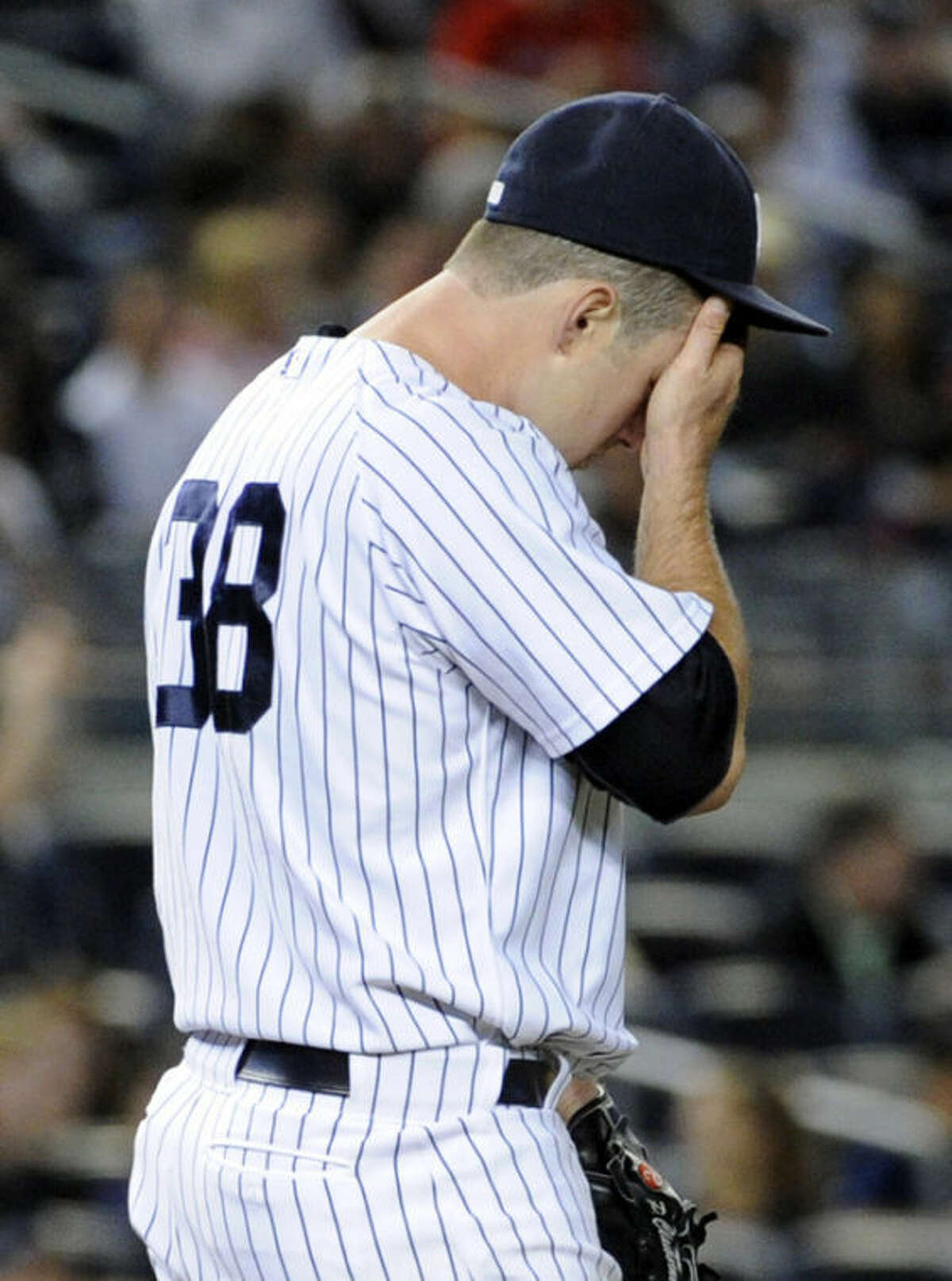 New York Yankees pitcher Preston Claiborne reacts as Boston Red Sox batter Shane Victorino (not shown) rounds the bases after hitting a two-run home run during the eighth inning of a baseball game, Friday, Sept. 6, 2013, at Yankee Stadium in New York. (AP Photo/Bill Kostroun)