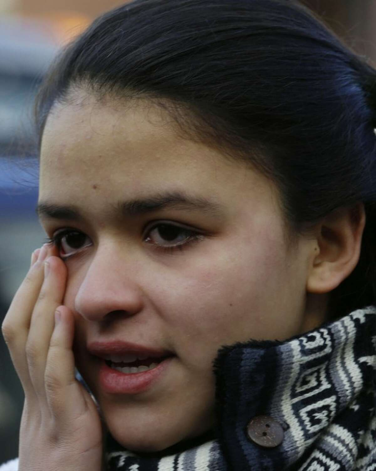 Isabella Jimenez, 12, reacts while talking to reporters about the shooting rampage from a day earlier when a gunman opened fire at Sandy Hook Elementary School, Saturday, Dec. 15, 2012, in Newtown, Conn. Jimenez said she might know the victims because she has done volunteer work with small children. The massacre of 26 children and adults at Sandy Hook Elementary school elicited horror and soul-searching around the world even as it raised more basic questions about why the gunman, 20-year-old Adam Lanza, would have been driven to such a crime and how he chose his victims. (AP Photo/Julio Cortez)