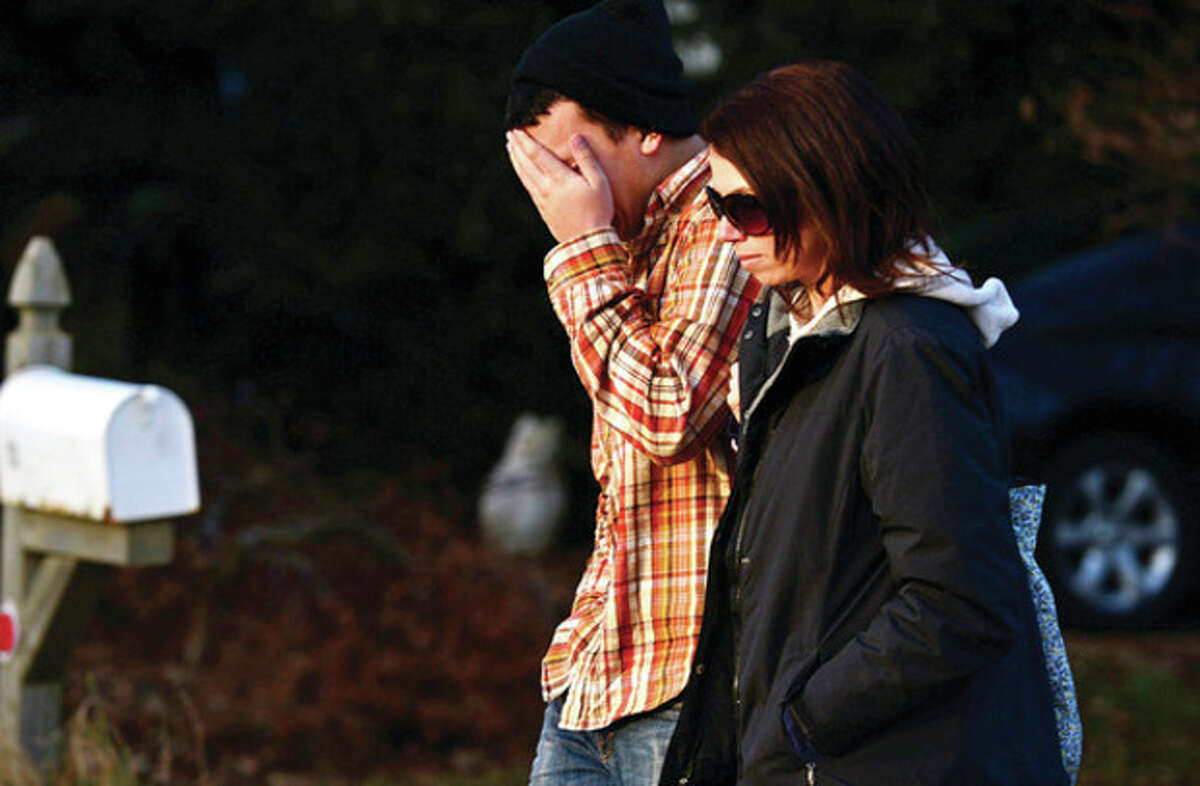 Hour photo / Erik Trautmann Unidentified visitors mourn the tragedy in Newtown Saturday afternoon at a makeshift memorial outside the school.