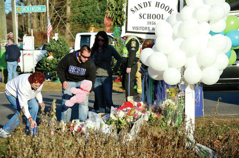 Visitors and residents mourn the tragedy in Newtown Saturday afternoon by putting out signs and leaving gifts at a makeshift memorial outside the school.Hour photo / Erik Trautmann / (C)2012, The Hour Newspapers, all rights reserved
