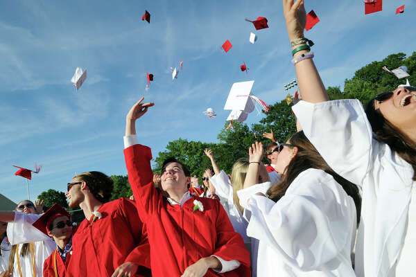 New Canaan High School graduates toss their caps in the air at the end of their graduation ceremony at New Canaan High School, Conn., Wednesday, June 15, 2016.
