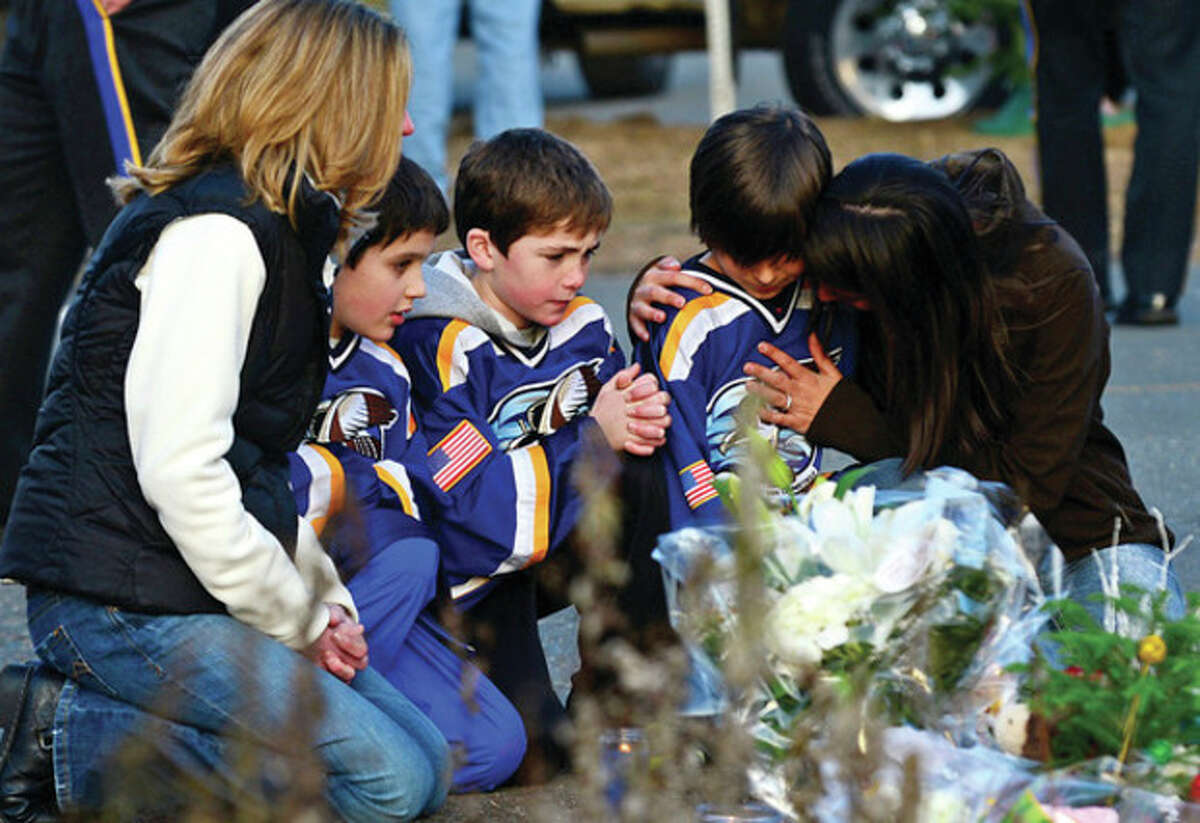 Hour photos / Erik Trautmann Above, from left, Jean Bradley, her son Matthew, Steven Turchetta, Ashton Baltes and his mother, Elonda Baltes, from East Lyme visit to pay respects and mourn the tragedy in Newtown Saturday afternoon at a makeshift memorial outside the school. Below, other visitors and residents put out signs and leave gifts at the makeshift memorial.