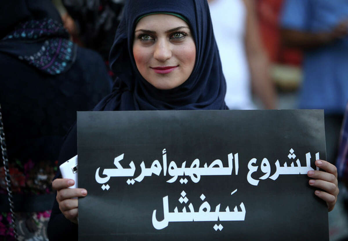 A Lebanese pro-Syrian regime supporter, holds a placard with Arabic that reads,