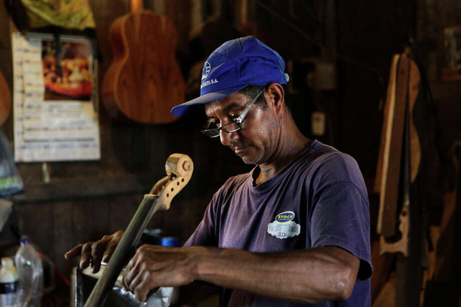 """In this Dec. 11, 2012 photo, Nicolas Gomez makes a violin out of recycled materials at his home in Cateura, a vast landfill outside Paraguay's capital of Asuncion, Paraguay. Gomez, a trash picker and former carpenter, was asked by Favio Chavez, the creator of """"The Orchestra of Instruments Recycled From Cateura,"""" to make instruments out of materials from the dump to help keep the younger kids occupied. """"I only studied until the fifth grade because I had to go work breaking rocks in the quarries,"""" said Gomez, 48. (AP Photo/Jorge Saenz) / AP"""