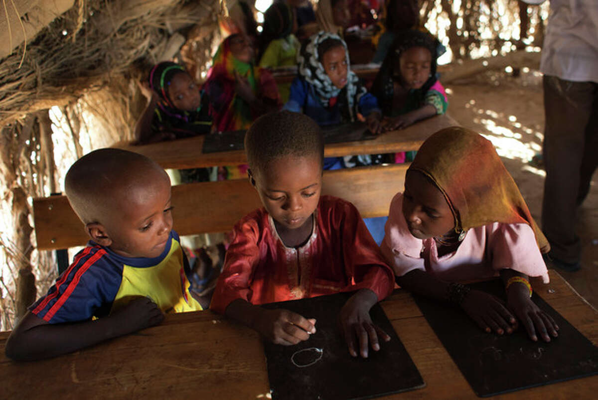 """In this Nov. 2, 2012 photo, 7-year-old Achta, right, and Youssouf, left, look on as Mahamat, center, struggles to copy a circle during a lesson on drawing the letter """"a"""" in the village of Louri in the Mao region of Chad. In this village where malnutrition has become chronic, children have simply stopped growing. In the county that includes Louri, 51.9 percent of children are stunted, one of the highest rates in the world, according to a survey published by UNICEF - more than half the children in the village. (AP Photo/Rebecca Blackwell)"""