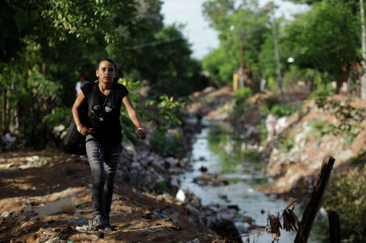 In this Dec. 11, 2012 photo, Tania Vera, 15, walks from her home alongside a polluted stream to practice with ?