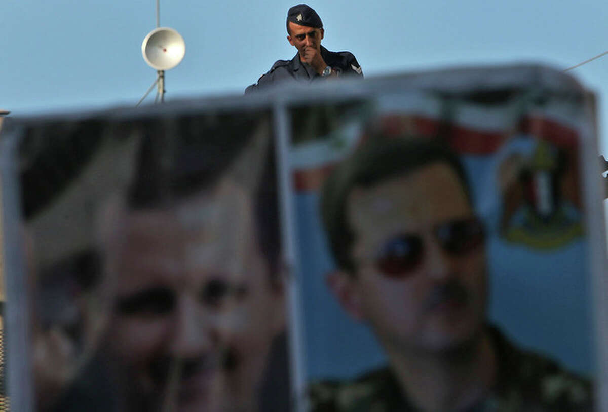 A Lebanese riot policeman, stands guard behind portraits of Syrian President Bashar Assad, during a demonstration held by Lebanese pro-Syrian regime supporters against a possible military strike in Syria, near the U.S. Embassy in Awkar, east of Beirut, Lebanon, Friday, Sept. 6, 2013. The prospect of a U.S.-led strike against Syria has raised concerns of potential retaliation from the Assad regime or its allies. The State Department ordered nonessential U.S. diplomats to leave Lebanon over security concerns and urged private American citizens to depart as well. (AP Photo/Hussein Malla)