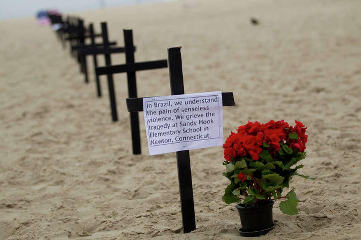 Crosses are set at the Copacabana Beach in Rio de Janeiro, Saturday, Dec. 15, 2012, in memory of the school shooting victims in Newtown, Conn. (AP Photo/Silvia Izquierdo)