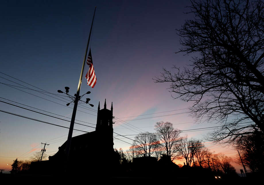 A U.S. flag flys at half-staff as vehicles drive on Main Street in downtown Newtown, Conn., as the sun rises the morning after a gunman opened fire inside a nearby elementary school, Saturday, Dec. 15, 2012. The man allegedly killed his mother at their home and then opened fire Friday inside the Sandy Hook Elementary school, massacring 26 people, including 20 children. (AP Photo/Julio Cortez) / AP