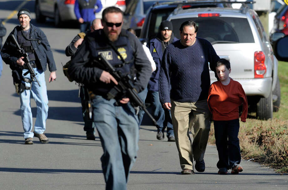 Parents leave a staging area after being reunited with their children following a shooting at the Sandy Hook Elementary School in Newtown, Conn. where authorities say a gunman opened fire, leaving 27 people dead, including 20 children, Friday, Dec. 14, 2012. (AP Photo/Jessica Hill) / FR125654 AP